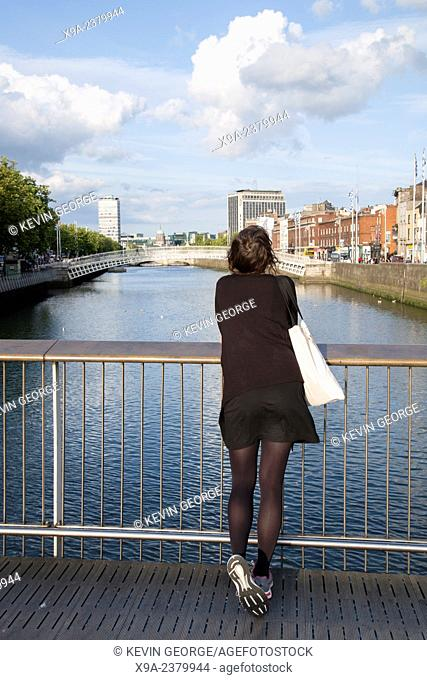 Young Woman on Millennium Bridge looking towards Ha'Penny Bridge, Dublin, Ireland