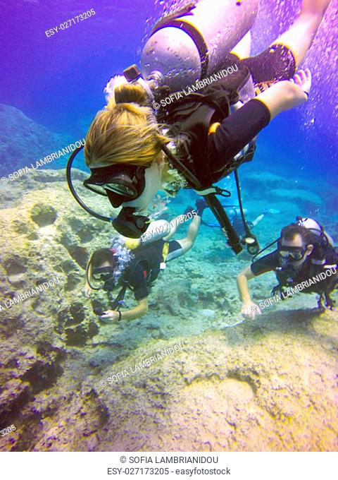 Young scuba divers, woman, man swimming underwater. View of the scuba diver gear, tank, regulator, mask, fins and bubbles in the deep blue sea of Protaras