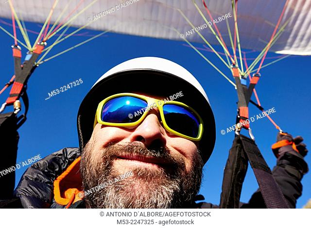 An adult caucasian man while paragliding