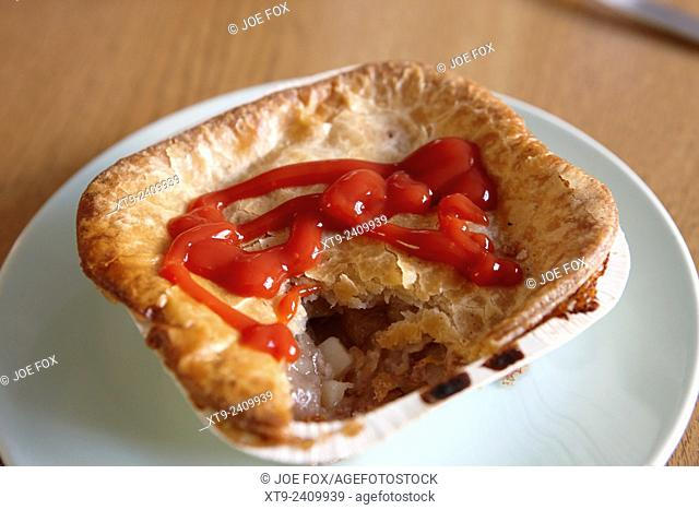 baked scouse pie in carton covered in tomato sauce
