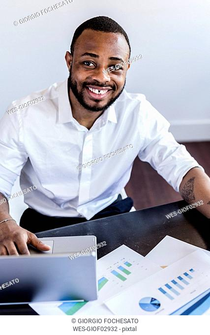 Portait of smiling man analysing data and using laptop at desk in home office