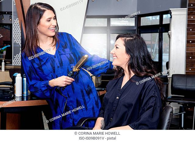 Stylist attending to customer in hair salon