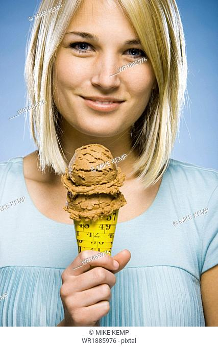 woman eating ice cream out of a tape measure cone