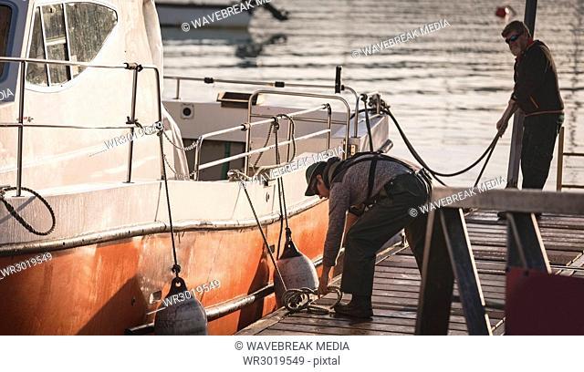 Fishermen tying buoy on boat