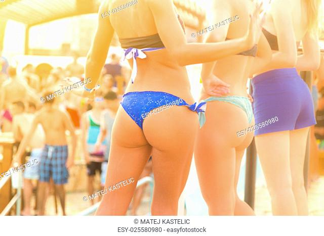 Sexy hot girl wearing brazilian bikini dancing on a beach party event in sunset. Crowd partying in shower of golden drops in background