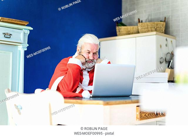 Frustrated Santa using laptop at home