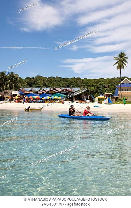 Photograph of the small islands Pulau Perhentian Kecil coast with two people canoeing while a boat shops umbrellas and a forest are noticeable at the background...