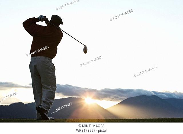 A golfer teeing off at sunrise