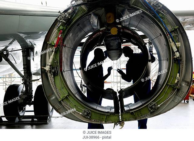 Engineers inspecting engine casing of passenger jet in hangar