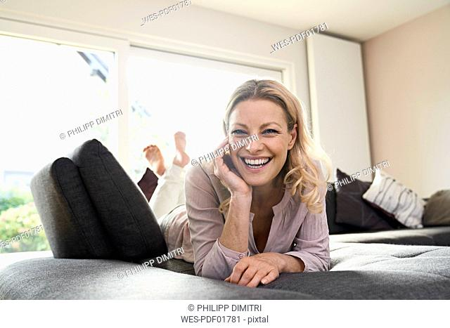 Portrait of laughing woman lying on couch at home