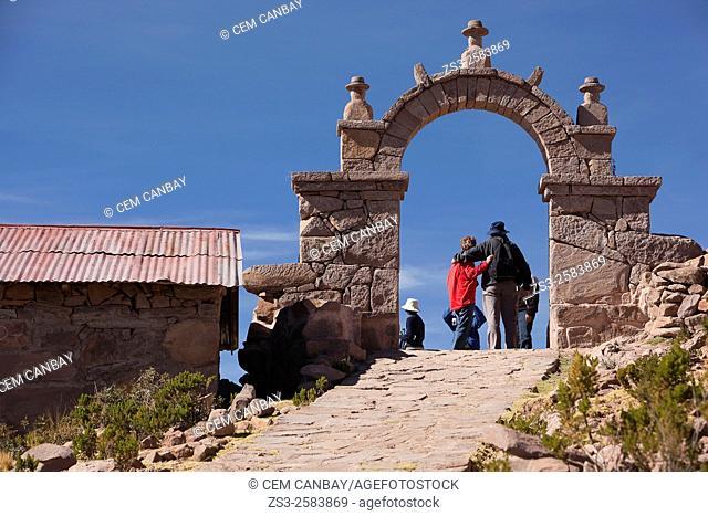 Tourists at a gate in Taquile island, Lake Titicaca, Puno Region, Peru, South America