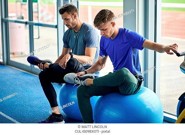 Runners stretching on exercise balls in indoor running track