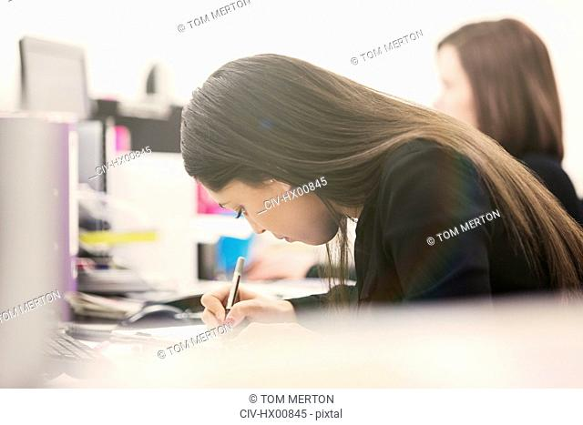Focused businesswoman writing at desk in office
