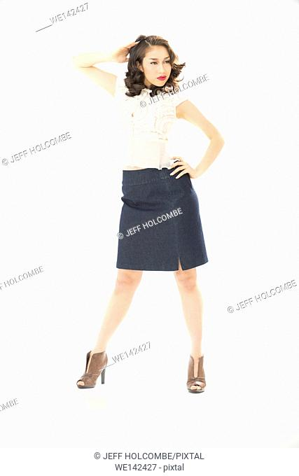 Beautiful young woman in white blouse and blue denim skirt, full length in brown heels, hand on hip, head turned aside