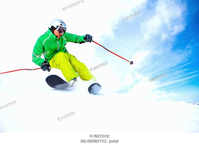 Skier, skiing downhill, low angle view