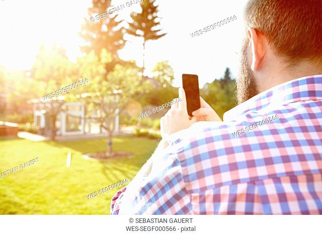 Young man with smartphone in garden, photografing his garden