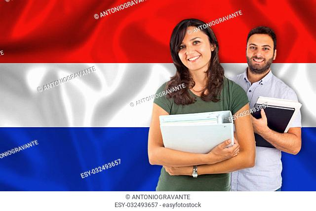Couple of young students with books over Dutch flag