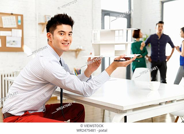 Business men in the studio with a housing model