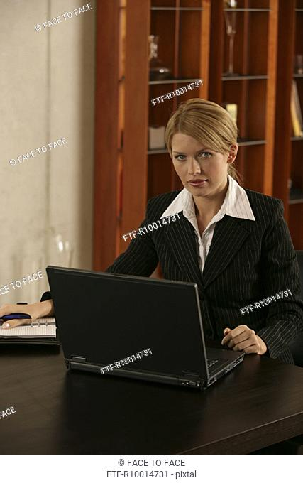 A blonde businesswoman working on her laptop in her office
