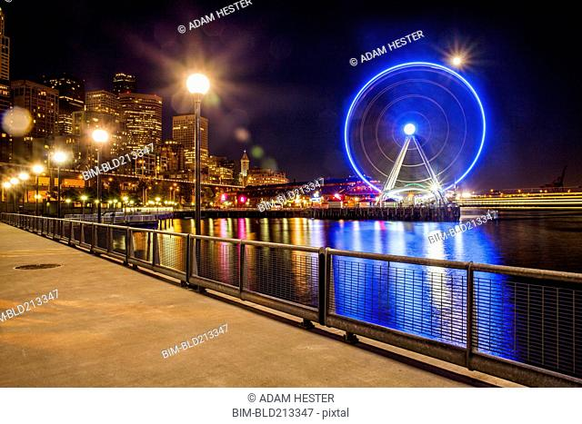 Illuminated ferris wheel on urban waterfront at night, Seattle, Washington, United States