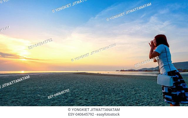 Happy women tourist raise hands at the mouth yelling and beautiful natural landscape of colorful sky and sea during a sunset at Nathon Sunset Viewpoint in Samui...