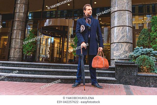 Confident businessman is waiting for someone near office building. He is carrying newspaper and umbrella with suitcase. Guy is looking aside pensively