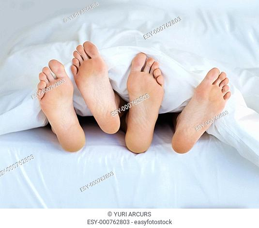 View of a couple's feet sticking out of the bed sheet while in bed