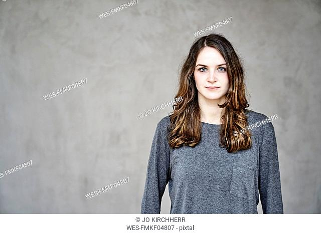 Portrait of confident young woman in front of grey wall