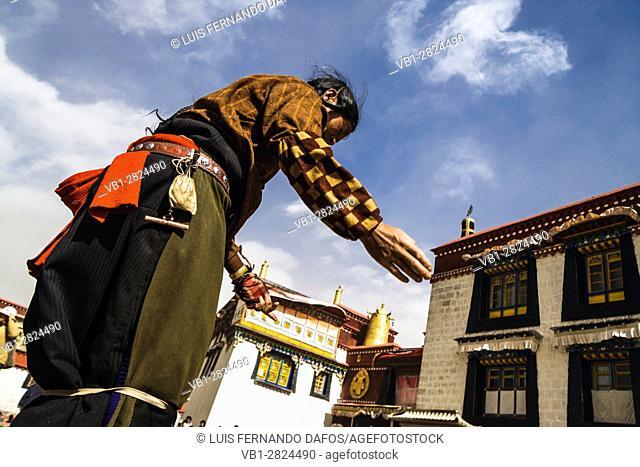 Pilgrim praying outside Jokhang Temple at Barkhor Square, Lhasa, Tibet