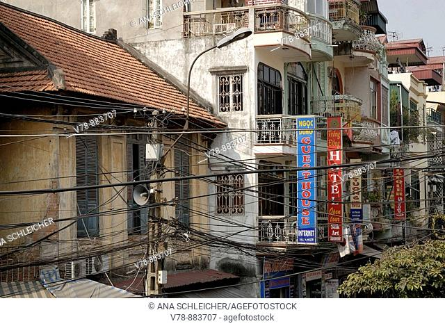 Street of the old town of Hanoi. Most of the old ocre houses have disappeared and cheap hotels have been built instead. Most of them have a narrow façade so as...