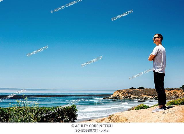 Man looking out over coast and sea, Cambria, California, USA
