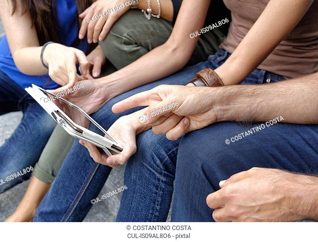 Group of friends looking at digital tablet, focus on tablet and hands