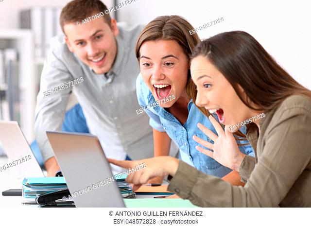 Three excited employees receiving good news on line at office