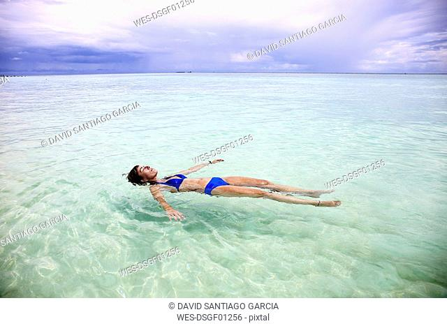 Maldives, Gulhi, woman floating in shallow water