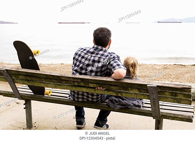 A father and his little girl sit on a bench and watch the ships anchored in the sea; Vancouver, British Columbia, Canada
