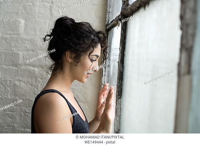 Happy young woman looking out of the window