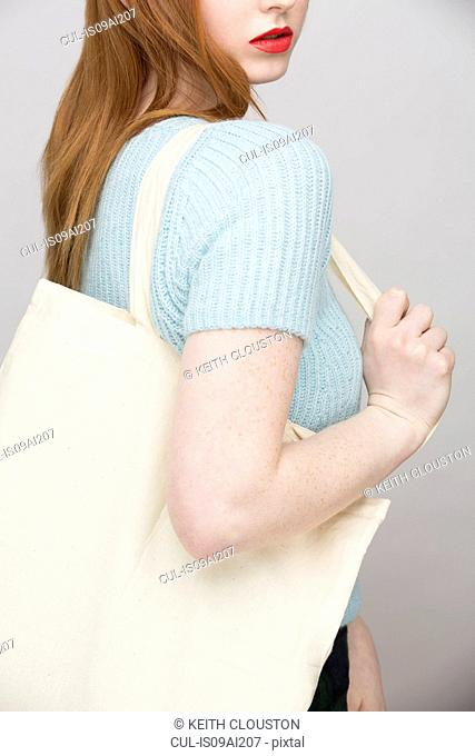 Cropped image of young woman carrying shopping bag