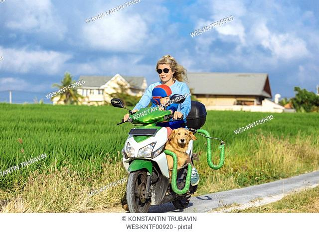 Woman with child and dog riding motor scooter on country lane