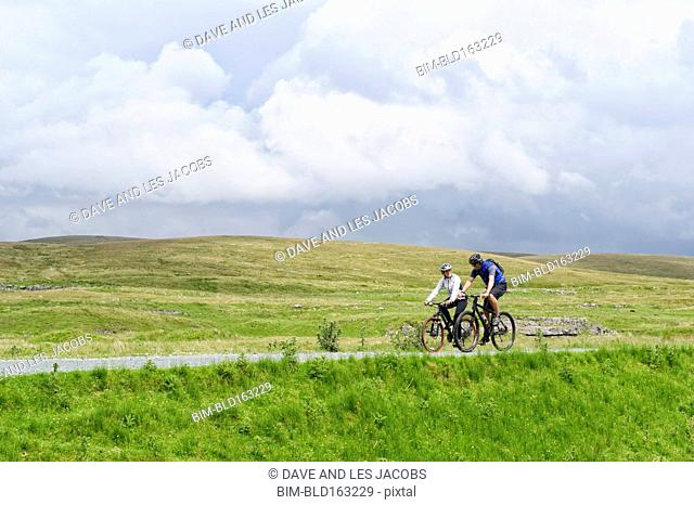 Caucasian couple riding mountain bikes on gravel road