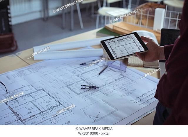 Mid section of architect using digital tablet at table