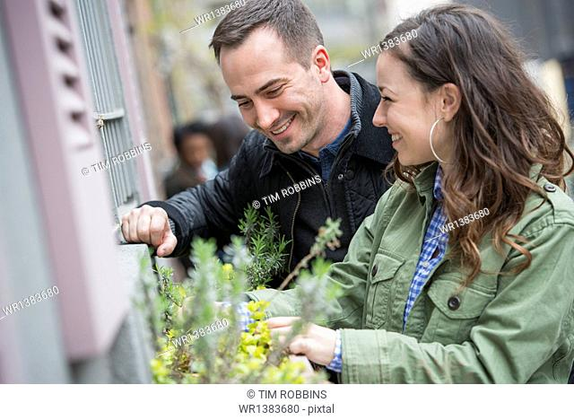 A man and a woman tending a window box on a city street. Spring flowers