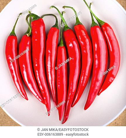 Closeup of plate with fresh raw red hot chili peppers