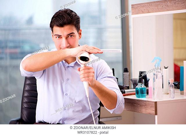 Handsome man in hair salon doing haircut