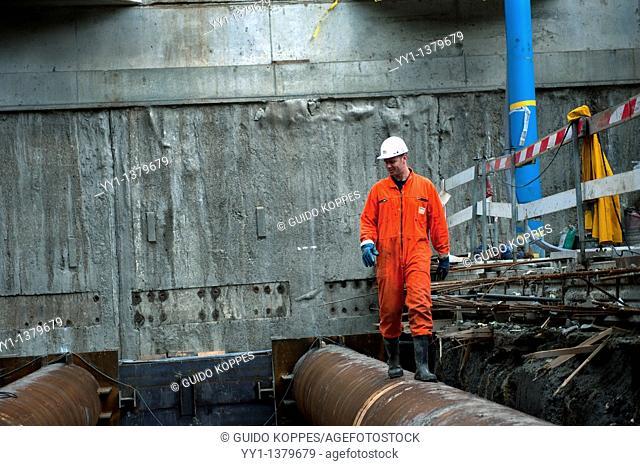 Rotterdam, Netherlands. A constructionworker walks alongside or over a tube, inspecting an underground parking garage under construction
