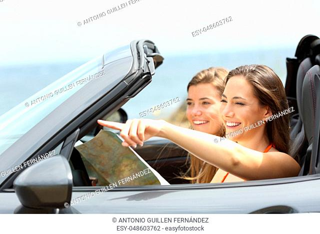Two happy tourists in a convertible car consulting guide and pointing landmarks on summer vacations