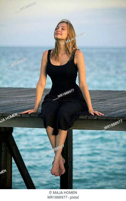 Young woman in sundress relaxes on a boardwalk, Lankayan Island, Borneo, Malaysia