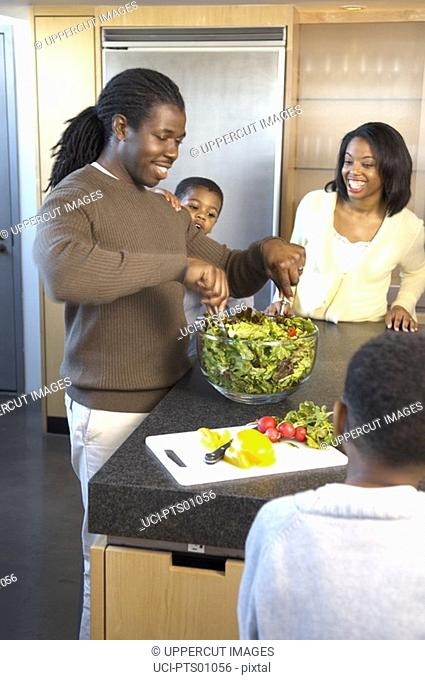 Family preparing meal in kitchen, father tossing salad