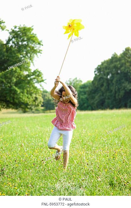 Girl running with pinwheel on meadow