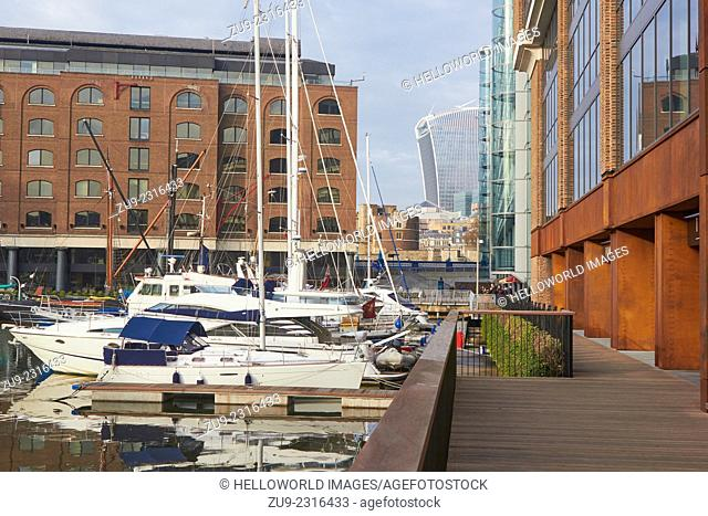 Luxury apartments and yachts in St Katherine Docks with City of London in background, London, England, Europe