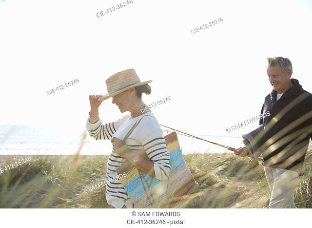 Mature couple with fishing rod walking in sunny summer beach grass